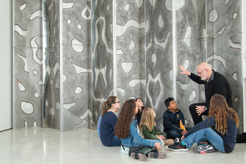 Older man gesturing to large abstract sculpture as sitting children watch him