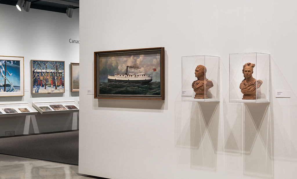 An exhibit in the Art Gallery of Windsor with framed paintings and two bust sculptures