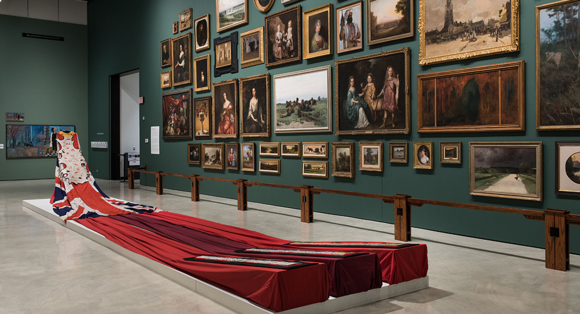 A green wall hung with framed paintings and a ceremonial garment with very long trail