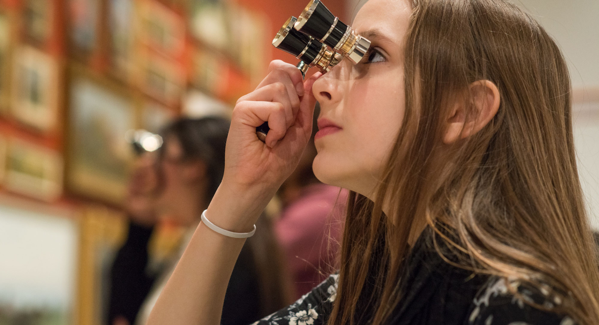 Young girls using special binoculars to look at framed art hung on a wall