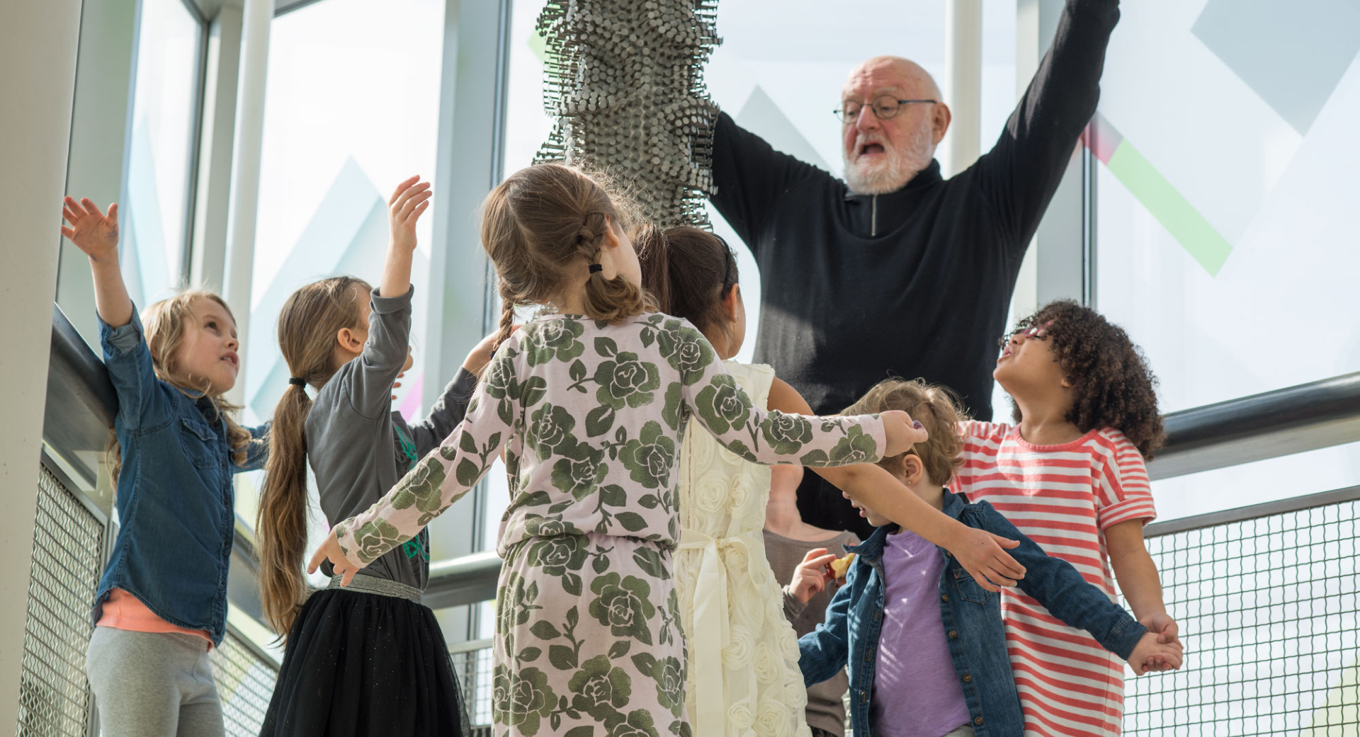 older man with a beard & glasses surrounded by children all raising their arms next to a sculpture